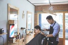 Парикмахер делая стрижку привлекательного человека в парикмахерскае Стоковые Фотографии RF