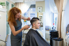 Парикмахер девушки с курчавыми красными волосами режет молодого, красивого парня в салоне красоты Стоковые Изображения RF