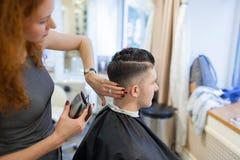 Парикмахер девушки с курчавыми красными волосами режет молодого, красивого парня в салоне красоты Стоковое фото RF