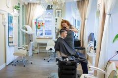Парикмахер девушки с курчавыми красными волосами режет молодого, красивого парня в салоне красоты Стоковое Изображение RF