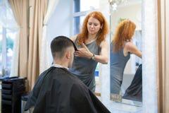 Парикмахер девушки с курчавыми красными волосами режет молодого, красивого парня в салоне красоты Стоковая Фотография