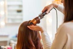 Парикмахер делает девушку стиля причёсок с длинными красными волосами в салоне красоты Стоковые Фото