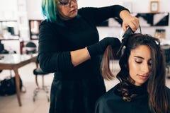 Парикмахер делает скручиваемости для женщины в салоне Стоковая Фотография