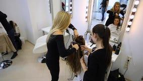 Парикмахер делает hairdress красивую девушку в салоне красоты видеоматериал