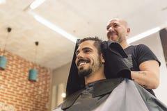 Парикмахер делая стрижку людей к привлекательному человеку стоковая фотография rf
