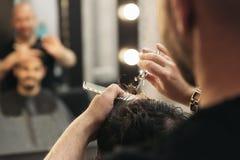 Парикмахер делая стрижку людей к привлекательному человеку стоковое изображение