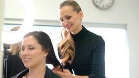 Парикмахер женщины вводя волосы в моду клиента в ее магазине акции видеоматериалы