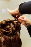 Парикмахер женщины делая стиль причёсок используя завивая утюг для длинных волос молодой женщины Стоковая Фотография