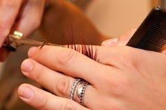 Парикмахер который режет волосы Стоковая Фотография
