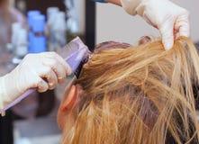 Парикмахер красит волосы ` s женщины в белизне, прикладывает краску к ее волосам в салоне красоты стоковое фото rf
