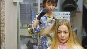Парикмахер, краска волос, белокурое усаживание в салоне красоты Краска парикмахера волосы сток-видео
