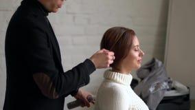 Парикмахер людей делая стиль причесок к девушке в салоне красоты сток-видео