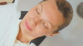 Парикмахер моет волосы молодой женщины сток-видео