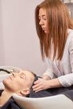 Парикмахер обтирая голову с полотенцем Стоковые Фото