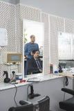 Парикмахер подготавливая бизнесмена для стрижки Стоковое Изображение RF