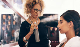 Парикмахер работая на волосах ` s женщины на салоне стоковые фото