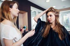 Парикмахер работая на женских стренгах клиппирования hairdo клиента s с штырями волос в студии парикмахерских услуг стоковые изображения rf