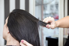 Парикмахер работая с красивыми волосами женщины в парикмахерские услуги sa Стоковое фото RF