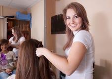 Парикмахер работая с long-haired девушкой стоковое фото
