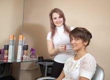 Парикмахер работая с long-haired девушкой стоковые изображения