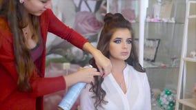 Парикмахер распыляет спрея для волос на брюнет пока делающ волос-сделайте акции видеоматериалы