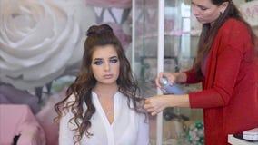 Парикмахер распыляет спрея для волос на модели брюнет пока делающ волос-сделайте видеоматериал