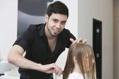 Парикмахер расчесывая волосы клиента на салоне стоковая фотография rf