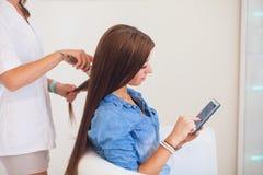 Парикмахер расчесывая женщину волос с мобильным телефоном в парикмахерских услугах Стоковое Изображение RF