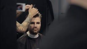 Парикмахер режет волосы в парикмахерскае сток-видео