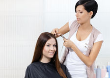 Парикмахер режет волосы женщины в парикмахере Стоковые Фотографии RF