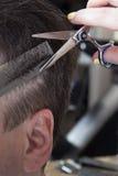 Парикмахер режет волосы красивого удовлетворенного клиента Стоковая Фотография