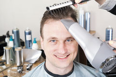 Парикмахер режет волосы красивого удовлетворенного клиента Стоковое фото RF