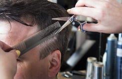 Парикмахер режет волосы красивого удовлетворенного клиента Стоковые Фото