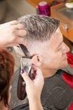 Парикмахер режет волосы стоковая фотография rf