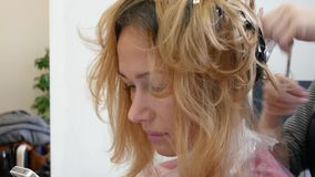 Парикмахер стилизатора делает расцветку волос, blonding, крася корни волос акции видеоматериалы