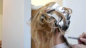 Парикмахер стилизатора делает расцветку волос, blonding, крася корни волос сток-видео