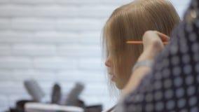 Парикмахер стилизатора делает стиль причесок для милой маленькой девочки в салоне красоты Парикмахерские услуги, вырезывание воло сток-видео