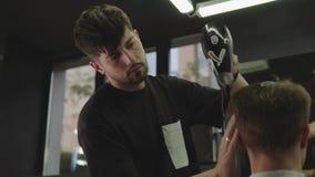 Парикмахер суша мужские волосы в салоне парикмахерских услуг r 4K сток-видео