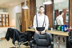 Парикмахер усмехаясь стулом в магазине стоковые фото