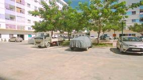 Паркуя график окруженный деревьями среди домов в городе сток-видео