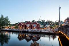 Парк атракционов Liseberg в Гётеборге, Швеции, с ресторанами и магазинами на заходе солнца Стоковое Фото