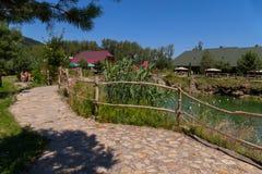 Парк воссоздания с большим прудом с путями выровнялся с лестницами кирпичей к коттеджам воды и отдыхая людям в Стоковые Изображения
