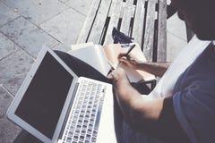 Парк города человека фото сидя и отправляя СМС тетрадь сообщения Изучающ в университете, проект деятельности Используя книгу Стоковое Изображение RF