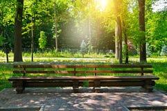 Парк, деревянные скамьи и восход солнца лета стоковое изображение