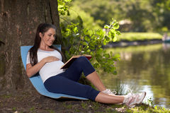 парк книги супоросый сидит детеныши женщины Стоковая Фотография