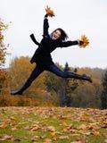парк листьев красивейшей девушки осени скача Стоковые Изображения RF