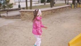 Парк маленькой девочки весной с кренами цвета ярк скольжений видеоматериал