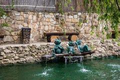 Парк на открытом воздухе Искусственные пруд и скульптуры зеленых лягушек фонтан Не-фонтана Каменные орнаменты Весна и сумма Стоковые Фото