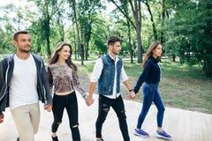 2 парни и девушки держа руки и идя через парк Стоковая Фотография RF