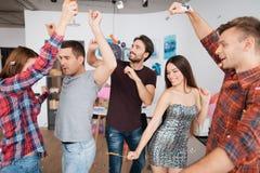 Парни и девушки танцуют на вечеринке по случаю дня рождения Они усмехаются и имеются потеху Стоковое Фото